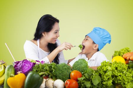 feed: Young Asian woman feeding her son with fresh vegetables using fork after cooking together