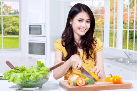 home cooking: Image of pretty Asian girl slicing vegetables while smiling at the camera in the kitchen