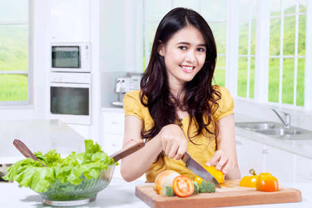 mujeres cocinando: Photo of pretty female model smiling at the camera while slicing vegetables to make salad in the kitchen