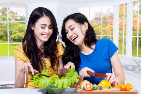 mujeres felices: Photo of two happy Asian women cooking vegetables salad in the kitchen at home