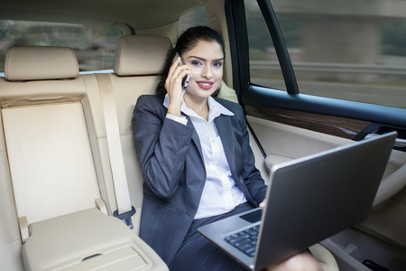 landline phone: Photo of Indian female entrepreneur talking on the phone while working with laptop computer in the car