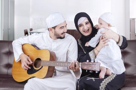 Portret van Happy Arabische familie zittend op de bank tijdens het spelen gitaar thuis