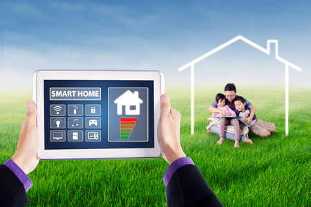 screen shot: Picture of hands holding tablet with smart house controller applications on the screen. Shot with young man and his children reading book under a house symbol Stock Photo