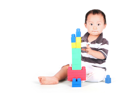 toddler boy: Portrait of baby playing with lego while sitting in studio, isolated on white background Stock Photo
