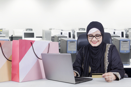 emoney: Businesswoman using credit card and laptop for shopping online with shopping bags on desk at office