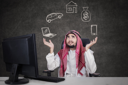 businessman working at his computer: Arabic young businessman working with computer while wearing traditional clothes and thinking his dreams Stock Photo