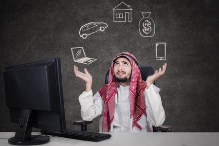 personas pensando: joven hombre de negocios árabe trabajando con el ordenador, mientras que desgasta la ropa tradicional y pensando en sus sueños