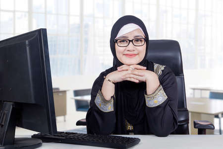 islam: Portrait of Arabic young woman working in the office while wearing headscarf and smiling at the camera Stock Photo