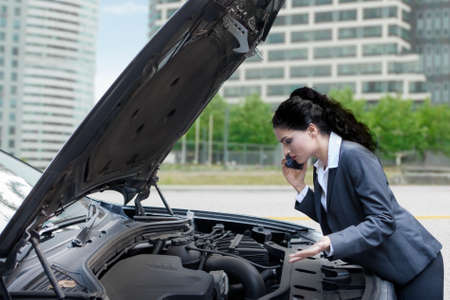 mechanics: Photo of Indian female worker calling a mechanic while looking at the broken car machine on the road