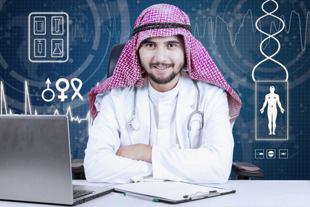 man doctor: Arabic male doctor smiling at the camera while sitting in the laboratory and folded his hand with laptop on desk
