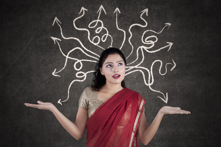 incertitude: Portrait of Indian woman thinking a solution while wearing sari clothes with arrow on the blackboard