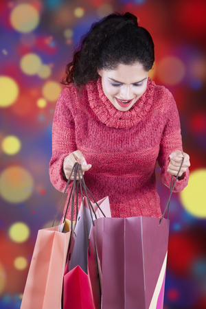 happy shopping: Happy indian woman wearing winter clothes and opens shopping bags with christmas background Stock Photo