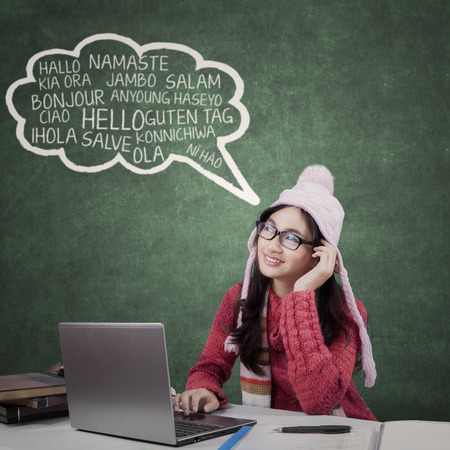 cloud technology: Female high school student wearing winter clothes in the classroom and learns foreign languages Stock Photo