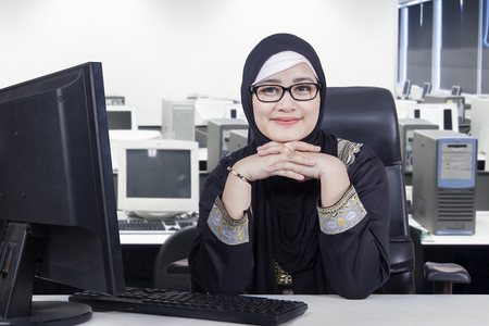 Foto von arabischen jungen Geschäftsfrau im Büroraum sitzen, während lächelnd in die Kamera und Schleier tragen mit Computer auf dem Schreibtisch