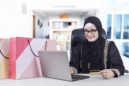 home business: Picture of Arabic young woman shopping online at home with notebook and credit card Stock Photo