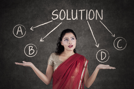 incertitude: Portrait of Indian young woman wearing sari clothes and looks confused to choose a solution
