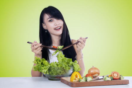 asian lifestyle: Portrait of pretty Asian woman smiling at the camera while holding two spoon to mix vegetables salad