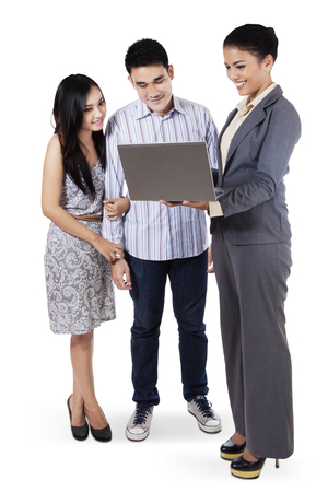 business people meeting: Young couple in a meeting with female consultant while standing on white background