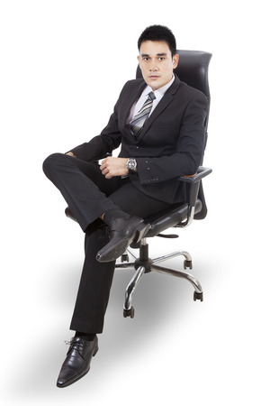 young businessman: Confident young businessman sitting on a chair isolated on white background