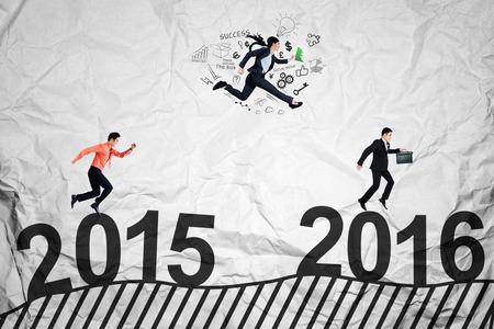 jovenes emprendedores: Tres jóvenes empresarios de correr y saltar por encima de los números 2015 a 2016 mientras compiten para conseguir el éxito Foto de archivo