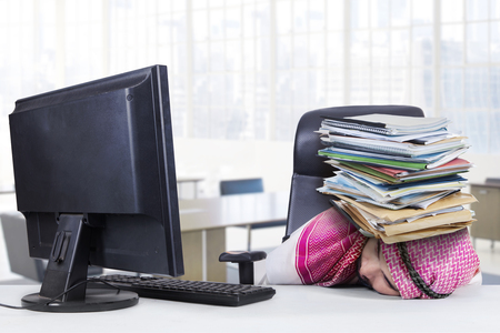 thobe: Stressful Arabian businessman sleeping on the table with a pile of paperworks on his head, shot in the office Stock Photo