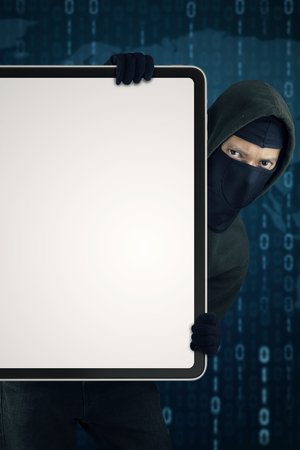 scammer: Male hacker wearing mask and holding a blank board with binary code background Stock Photo