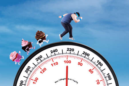 lb: Picture of young overweight person escaping from cupcakes while running on the scale Stock Photo