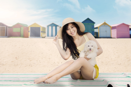 beach mat: Portrait of a beautiful girl with maltese dog sitting on the mat near the beach huts