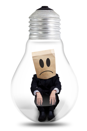 Image of a confused male entrepreneur with cardboard head, sitting inside a light bulb. Isolated on white background