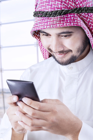 thobe: Arabian businessman using a smartphone to send message in the airport