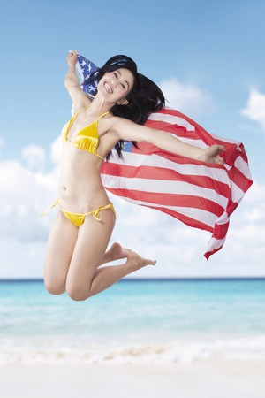 asian american: Picture of a joyful woman jumping on the beach while holding American flag Stock Photo