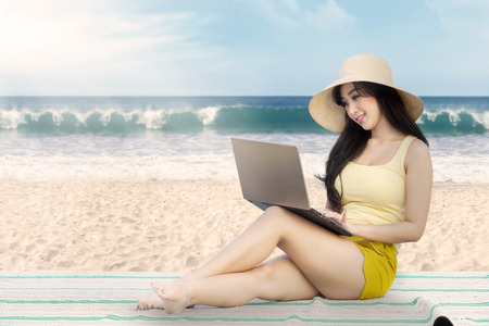 beach mat: Attractive young woman working with a laptop while sitting on the mat at the beach Stock Photo