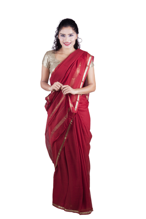 indian saree: Portrait of a pretty Indian woman standing in the studio while wearing a red saree and smiling at the camera Stock Photo