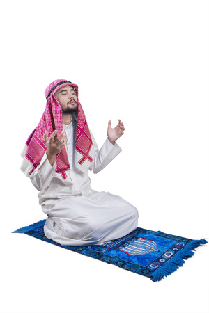 devout: Portrait of devout Arabian person sitting on the carpet while praying to the Allah, isolated on white background