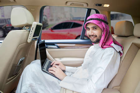 riches adult: Picture of Arabic businessman working in the car with a laptop and smiling at the camera