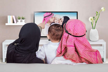 mujer viendo television: Arabian family sitting on the sofa while looking at their photo on the television, shot at home