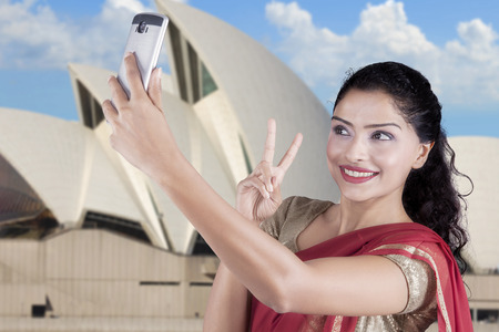 indian culture: Pretty Indian woman taking selfie photo with a smartphone at Opera House in Sydney