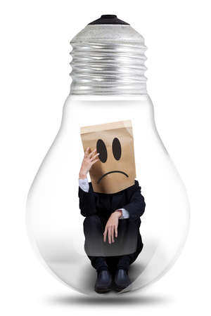 captivity: Thoughtful businessman with cardboard head sitting inside a light bulb, isolated on white background