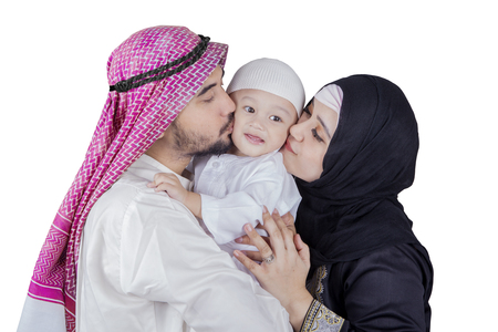 arabic boy: Portrait of a cute little Arabic boy kissed by his parents in the studio, isolated on white background