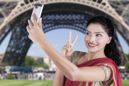 take a history: Beautiful Indian woman wearing traditional clothes and takes selfie picture at Eiffel Tower