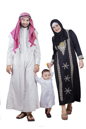 holding hands while walking: Portrait of happy Arabic family walking in the studio while holding hands and smiling at the camera