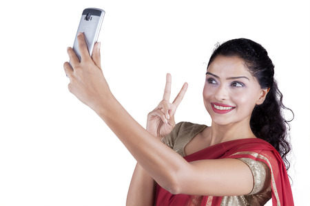 Beautiful Indian woman using smartphone to take selfie picture while wearing a saree clothes in the studio Stock Photo