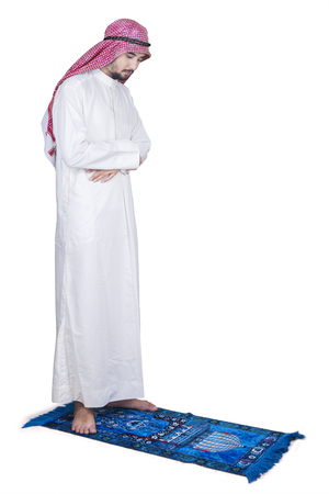 religious clothing: Full length of Arabic man praying in the studio above a carpet while wearing traditional clothes