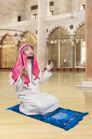 muslim pray: Portrait of middle eastern man sitting in the mosque while praying to the GOD Stock Photo