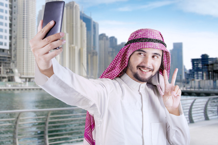 thobe: Happy Arabian person using a mobile phone to take selfie picture in the city