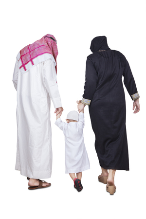 middle eastern clothes: Back view of muslim family wearing islamic clothes and walking together in the studio, isolated on white background