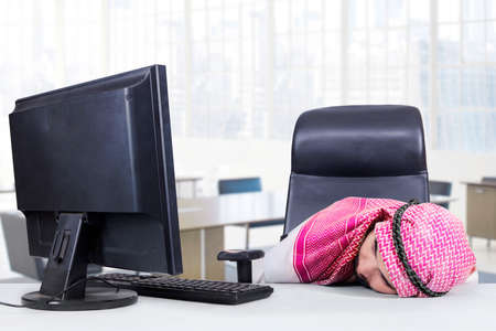 thobe: Image of Arabian businessman wearing headscarf and sleeping in the office with computer on the table