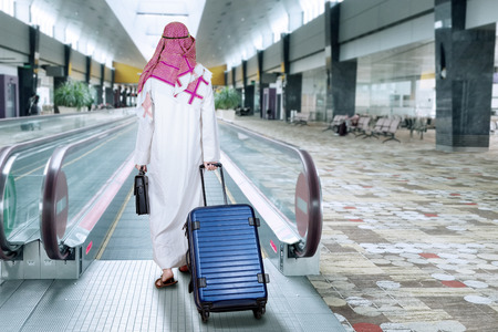 Middle eastern businessman doing business trip and walk in the escalator at airport while carrying luggage