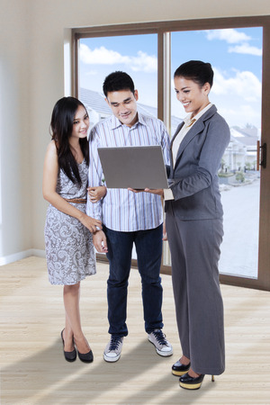 house windows: Female real estate agent showing a laptop to young couple before they purchase a house Stock Photo