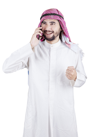 thobe: Portrait of a successful Arabian businessman standing in the studio while talking on the mobile phone Stock Photo